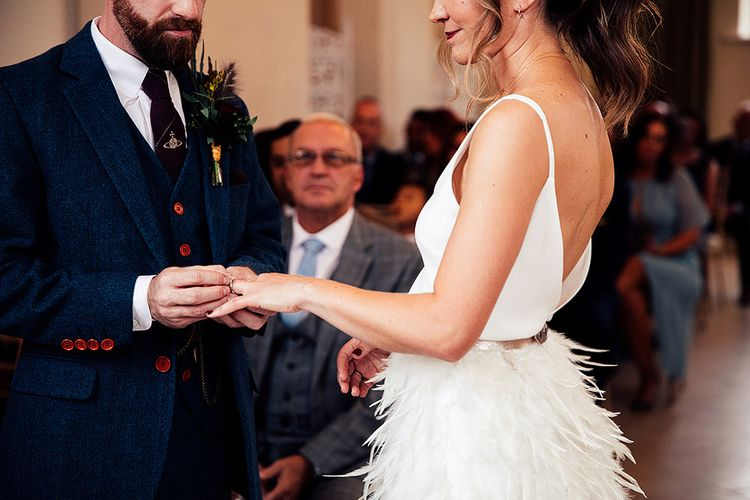 Bride in Charlie Brear Payton Bridal Gown & Piora Feather Skirt and Groom in Three Piece Wool Suit Exchanging Vows