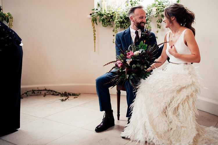 Bride in Charlie Brear Payton Bridal Gown & Piora Feather Skirt and Groom in Three Piece Wool Suit