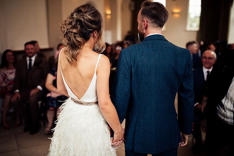 Bride in Charlie Brear Payton Bridal Gown & Piora Feather Skirt and Groom in Three Piece Wool Suit Just Married