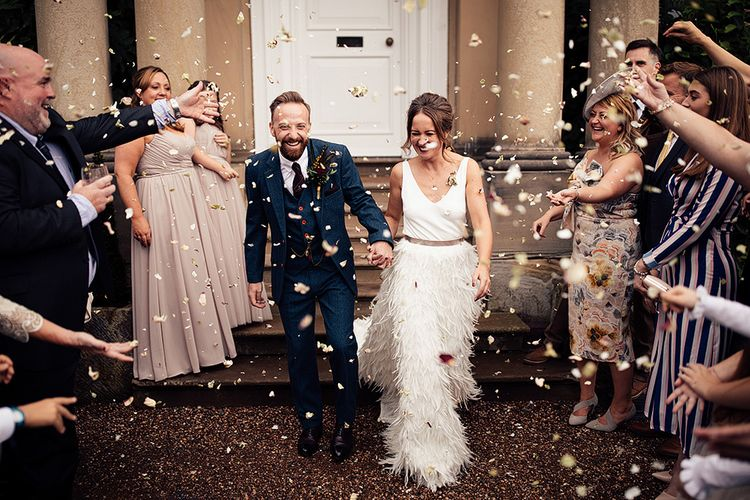 Confetti Moment with Bride in Charlie Brear Payton Bridal Gown & Piora Feather Skirt and Groom in Three Piece Wool Suit