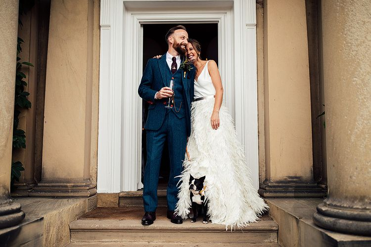 Bride in Charlie Brear Payton Bridal Gown & Piora Feather Skirt and Groom in Three-piece Wool Suit with Their Pet Pug
