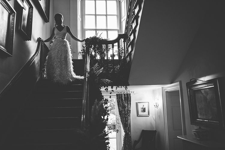 Bride Walking Down the Stairs  in Charlie Brear Payton Bridal Gown & Piora Feather Skirt