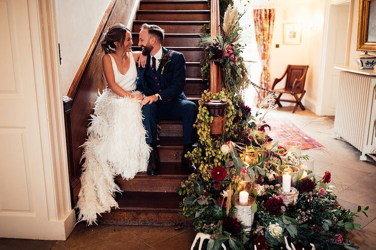 Bride Sitting on The Stairs  in a Charlie Brear Payton Bridal Gown & Piora Feather Skirt with Her Groom in a Navy Suit