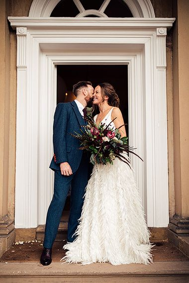 Bride in a Charlie Brear Payton Bridal Gown & Piora Feather Skirt and Groom in a Navy Suit