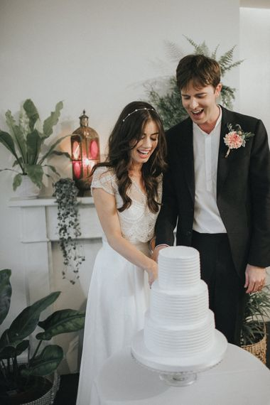 Cutting the Cake | Bride in Suzanne Neville Bridal Separates | Groom in Gieves and Hawkes Suit | Intimate Wedding at The Olde Bell Pub, Berkshire | Revival Rooms Floral Design, Decor & Styling | Grace Elizabeth Photo & Film
