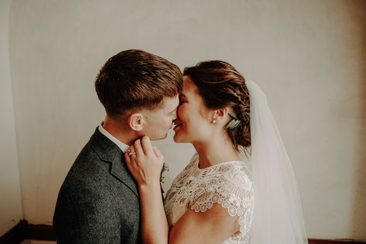 Bride wearing a lace top over her dress teamed with an up-do and veil for relaxed autumn wedding