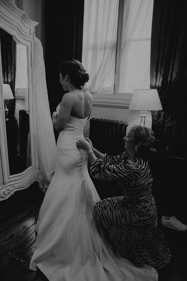 Back of brides strapless dress with button back detailing and up-do hair style