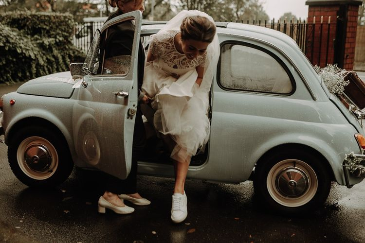 Bride arriving in vintage Fiat 500 wearing white trainer bridal shoes at autumn wedding in Manchester