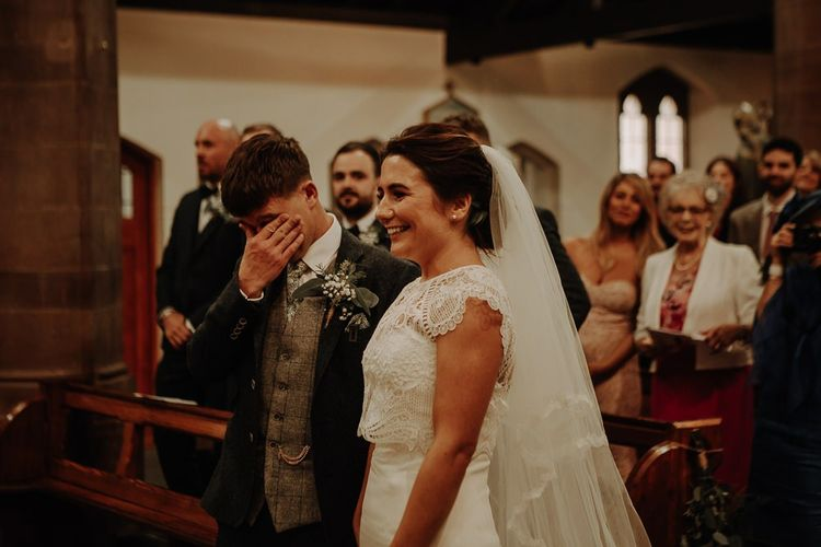 Bride wearing lace top over strapless dress with groom wearing floral buttonhole at church ceremony