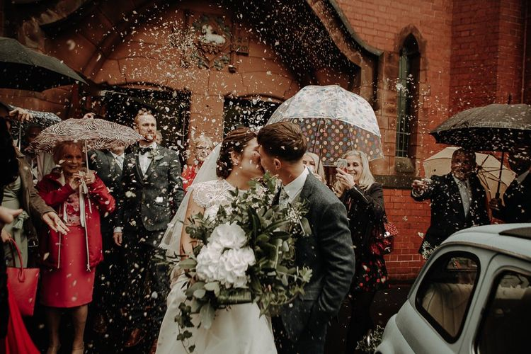 Bride and groom confetti shot with white hydrangea bouquet and bridal lace top over strapless dress