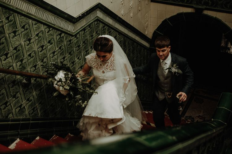 Bride and groom steal a moment wearing lace bridal top and long veil at Victoria Baths