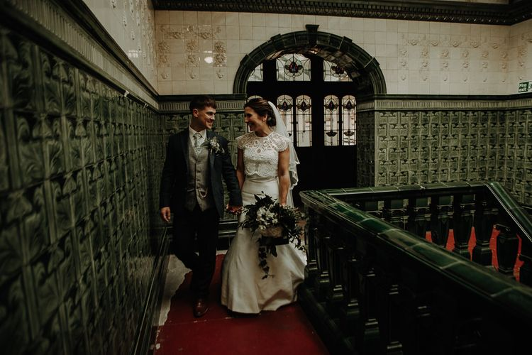 Bride wearing white lace top over strapless dress with white hydrangea bouquet at Victoria Baths