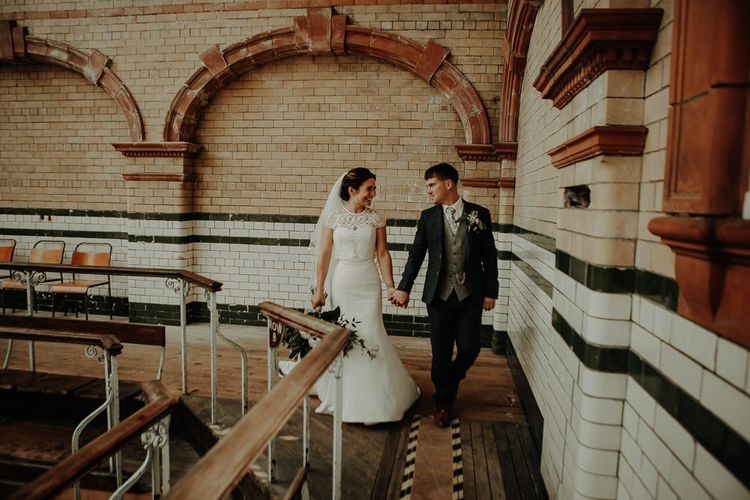 Bride and groom steal a moment at Victoria Baths wedding wearing three piece suit and buttonhole