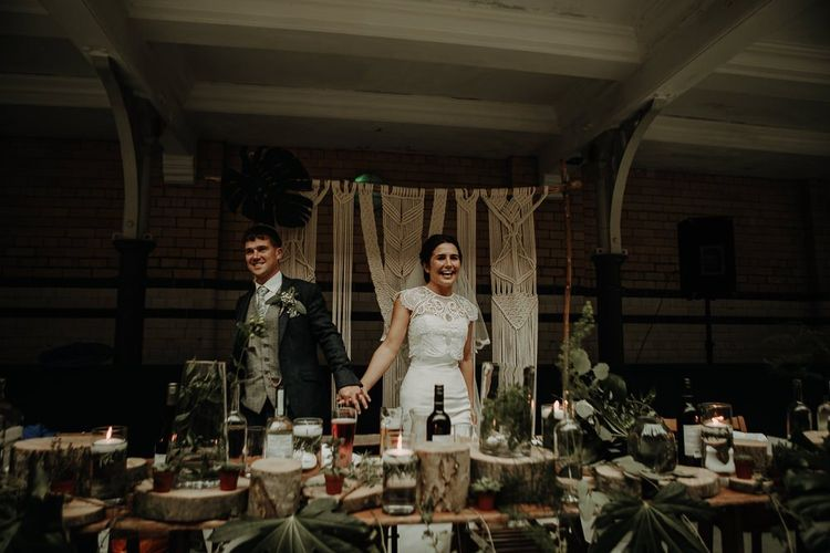 Bride and groom with DIY decor and macramé wall hanging