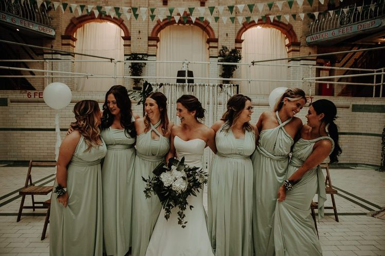 Bride wearing strapless dress and her bridesmaids wearing sage dresses