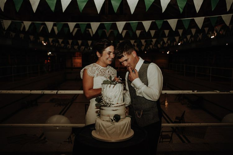Bride and groom cut the cake with semi-naked tier and botanical style foliage decor