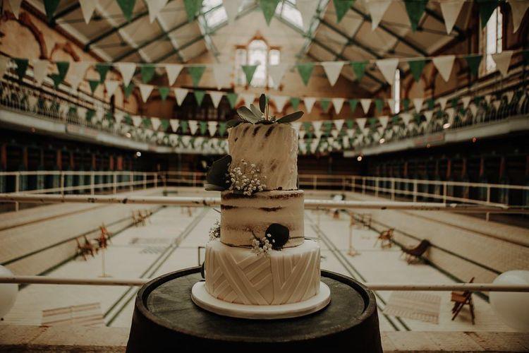 White wedding cake with semi-naked tier and botanical foliage decoration