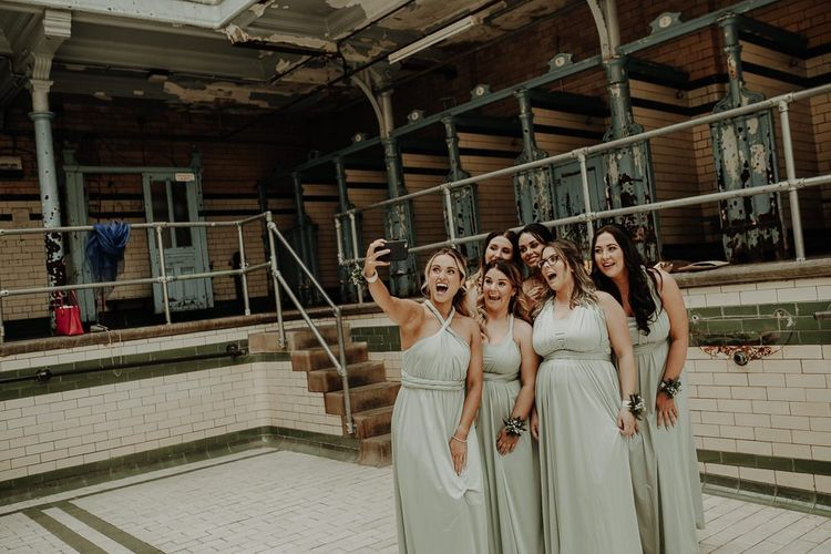 Bridesmaids pose for a selfie wearing sage colour dresses at botanical styled reception