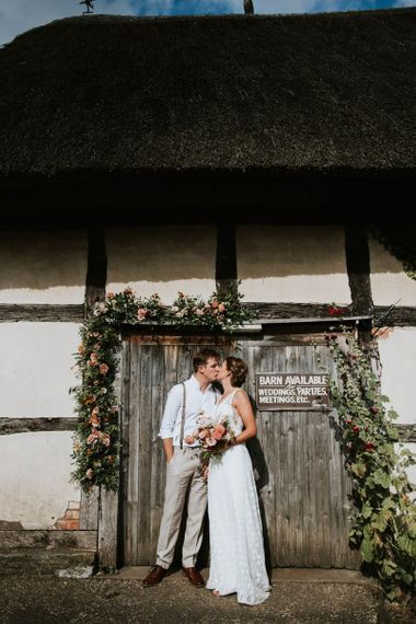 Bride and groom kiss with dahlia and rose wedding bouquet  and barn door decoration