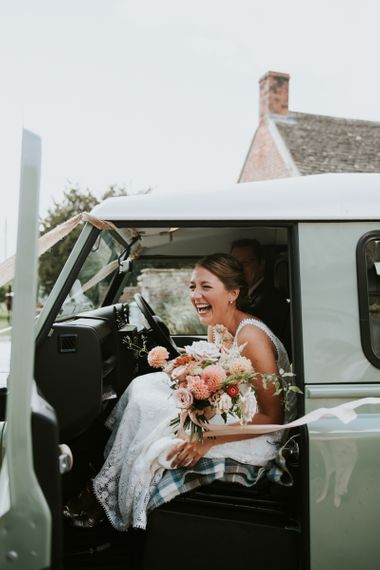 Bride on the way to the ceremony in mint green Land Rover and dahlia wedding bouquet