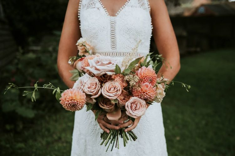 Bride with blush pink dahlia and rose wedding bouquet