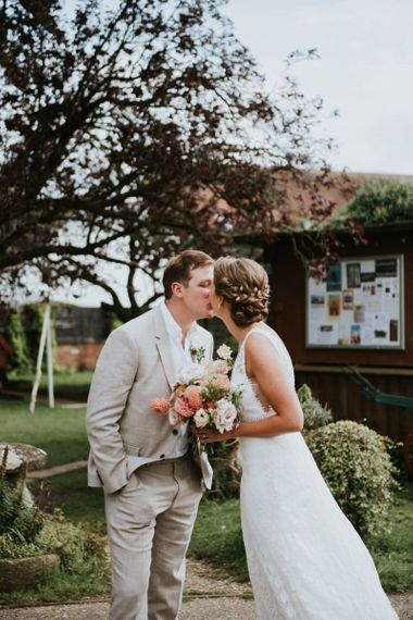 Bride and groom kiss with dahlia and rose wedding bouquet