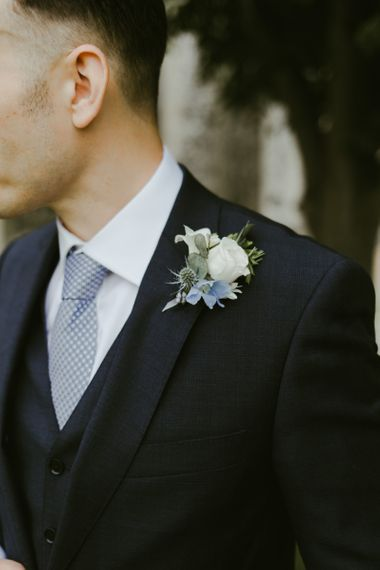 White flower buttonhole with blue suit and tie