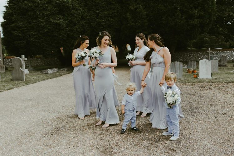 Bridesmaids in blue dresses arrive at church ceremony