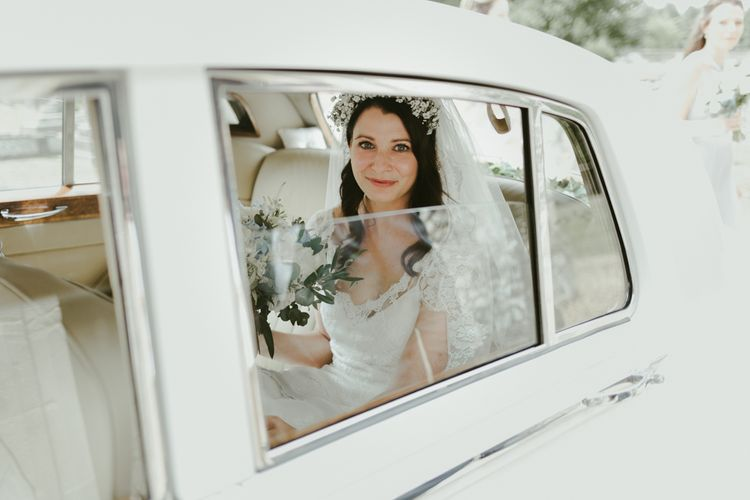 Bride arrives in classic white wedding car