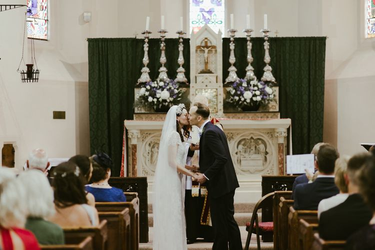 Bride and groom kiss at Church wedding ceremony