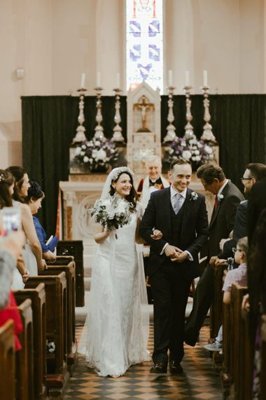 Newlywed couple walk back up the aisle