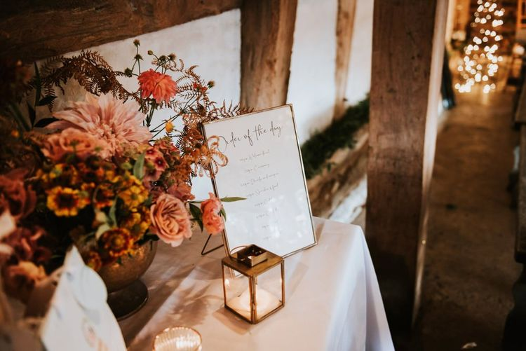 Wedding signs with tea lights and blush dahlia wedding flowers at barn reception