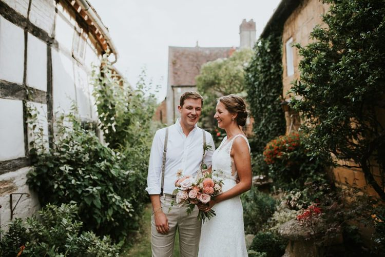 Bride in lace dress and groom in braces with dahlia wedding bouquet outside barn reception