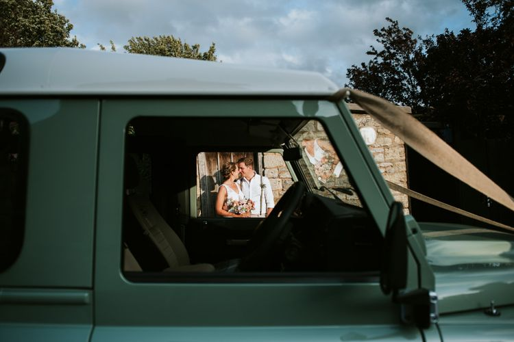 Bride and groom kiss next to mint green Land Rover with ribbon decoration