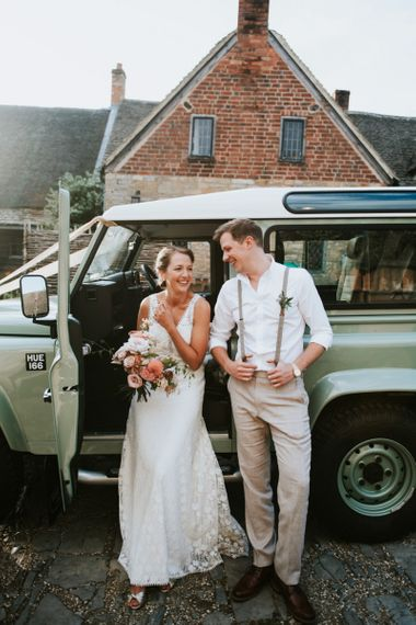 Bride in lace wedding dress and groom in braces with dahlia wedding bouquet next to mint green Land Rover