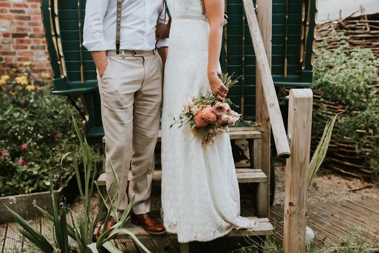 Bride in lace wedding dress with dahlia bouquet outside barn styled pub reception