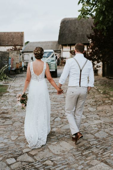 Back of brides lace dress with groom in braces and mint grey land rover transportation