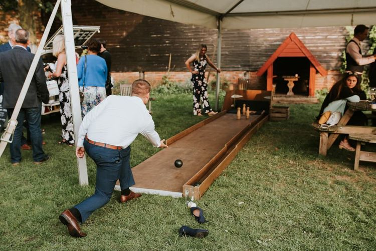Guests enjoying outdoor bowling alley at summer barn reception