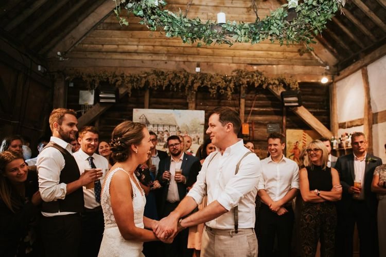 Bride and grooms first dance in barn reception with fairy lights and green leaf decoration
