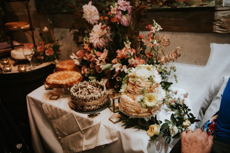 Mixture of homemade cake displayed on a table with dahlia flower decoration at summer pub reception