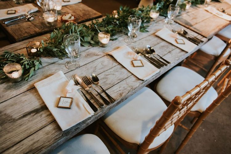 Table decor with tea light candles and left details at barn reception