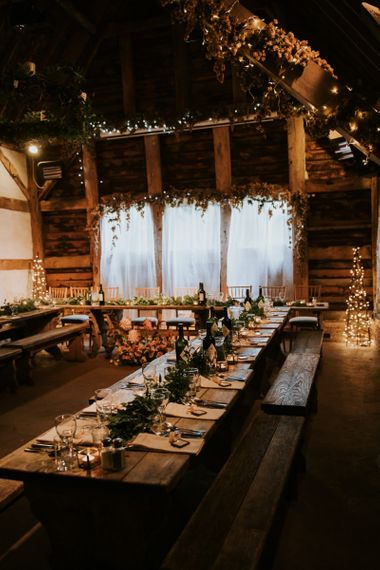 Table decor with leaf detailing and bench seating at barn reception