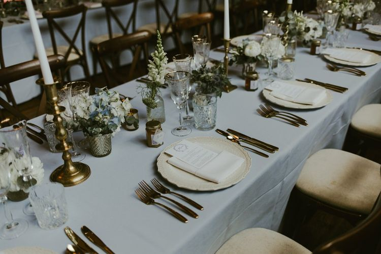 Wedding breakfast table decor with flowers and gold candlesticks