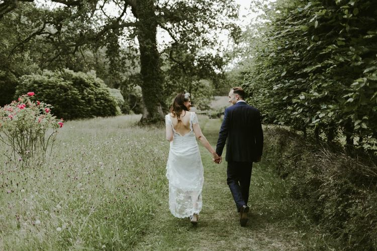 Bride and groom walk through the grounds of Ramster Hall