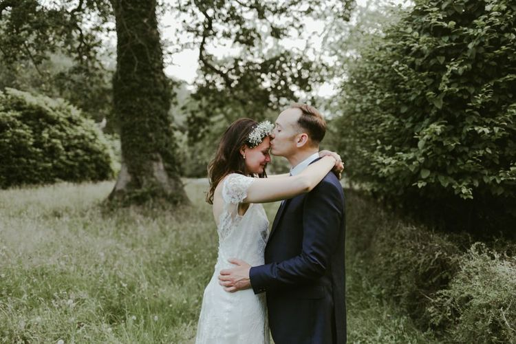 Groom kisses bride who wears lace dress and flower crown