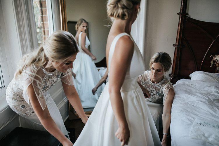 Wedding Morning Bridal Preparations with Bridesmaids Helping The Bride Get Dresses into Her Jesus Peiro Wedding Dress