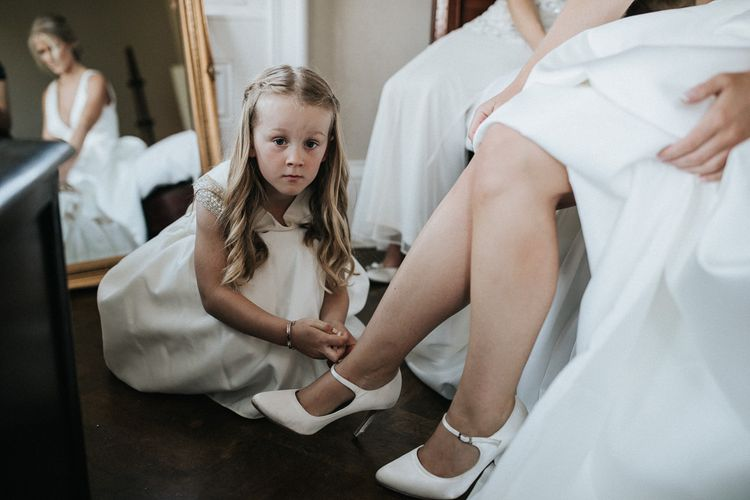 Flower Girl Helping The Bride Put On Her John Lewis Shoes