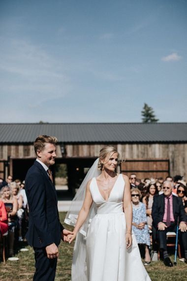 Bride in Jesus Peiro Wedding Dress and Groom in Dark Navy Suit at the Outdoor Wedding Ceremony Altar