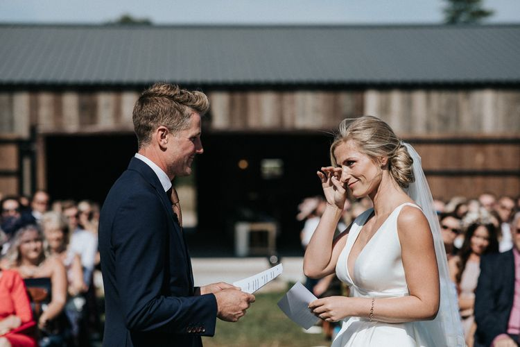 Emotional Bride in Jesus Peiro Wedding Dress and Groom in Dark Navy Suit Saying Their Vows at their Outdoor Wedding Ceremony