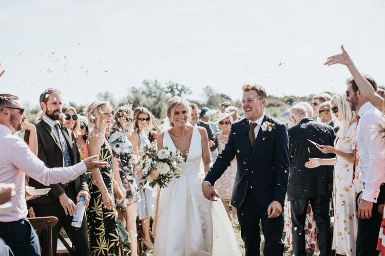 Confetti Moment with Bride in Jesus Peiro Wedding Dress and Groom in Dark Navy Suit